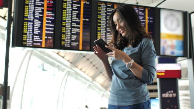 Teléfono de uso mujer en aeropuerto