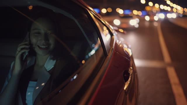街を通って車に乗って電話を使用している女性は夜に家に帰ります - タクシー点の映像素材/bロール