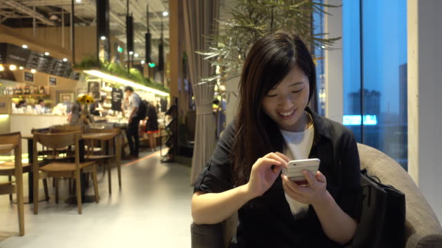 Woman using phone in coffe