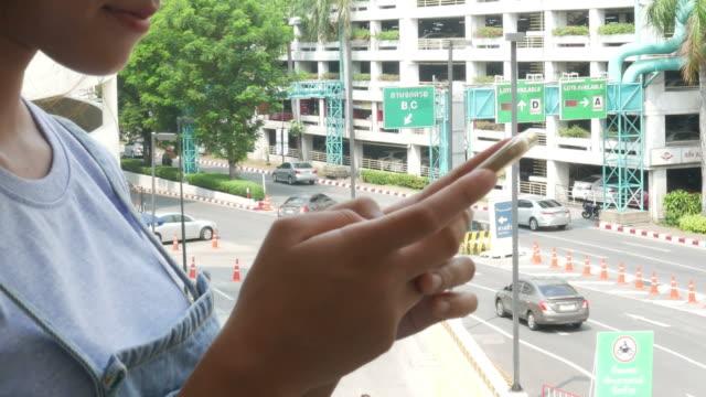Femme à l'aide de téléphone en stationnement, effectuer un zoom arrière