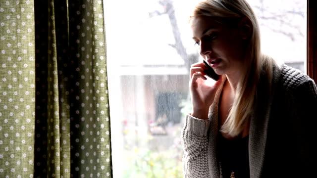 Woman using phone near window
