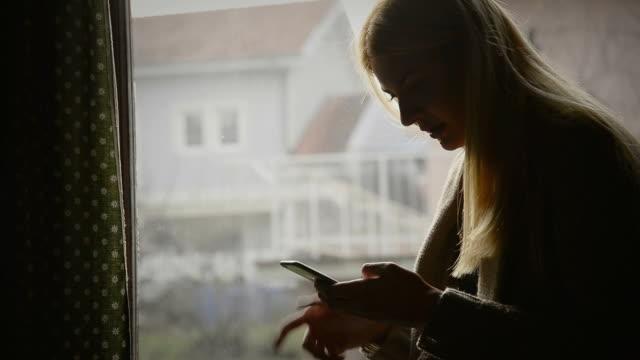 Frau mit Telefon in der Nähe vom Fenster nachdenkt.