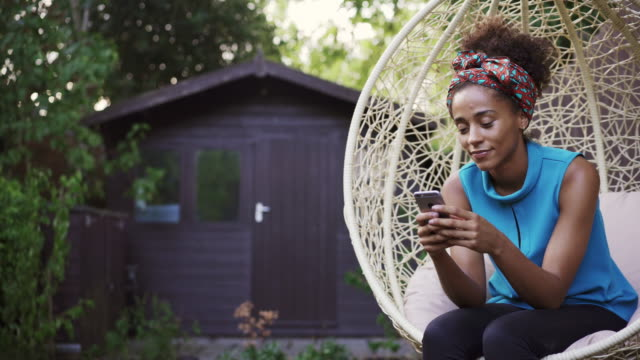 woman using phone on garden swing chair - mid adult stock videos & royalty-free footage