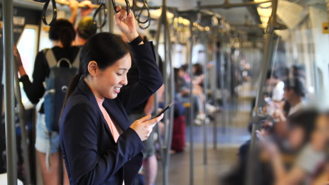 woman using phone on train - riding stock videos & royalty-free footage