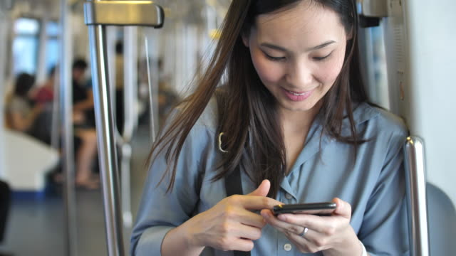 Woman using phone on Train