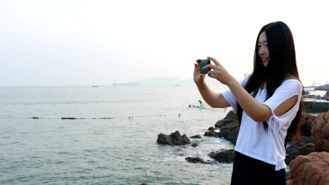 Woman using phone photographing landscape