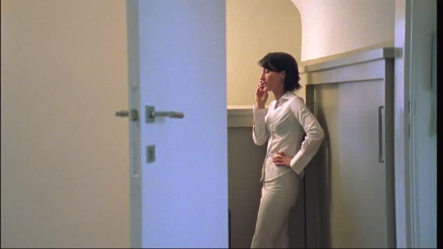 ms, woman using phone standing in doorway, brussels, belgium - bedroom doorway stock videos & royalty-free footage