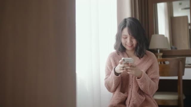 女人用手機,思考,然後在酒店房間微笑著回應。 - 回答 個影片檔及 b 捲影像
