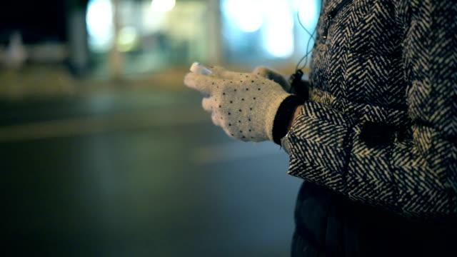 vídeos y material grabado en eventos de stock de mujer usando teléfono - abrigo de invierno