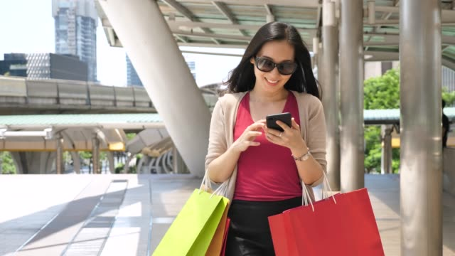 woman using phone walking with shopping bag in city, woman lifestyle - fare spese video stock e b–roll