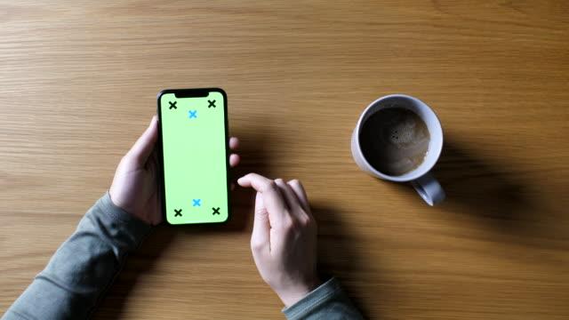 stockvideo's en b-roll-footage met vrouw met behulp van telefoon met groen scherm bij koffie shop, oogpunt, iphone x - draagbaarheid