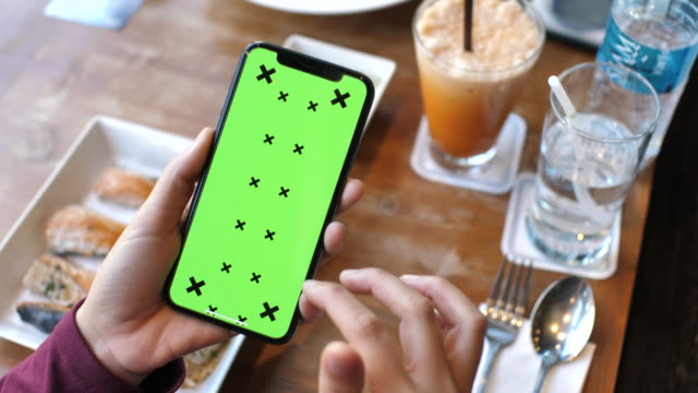 Woman Using phone with green screen in Restaurant