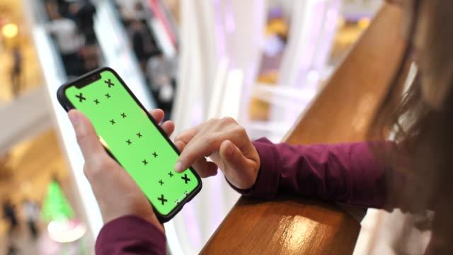 緑色の画面で携帯電話を使用しての女性 - スクロール点の映像素材/bロール