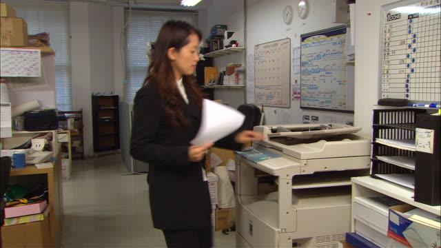 stockvideo's en b-roll-footage met ms, woman using photocopy machine in office - kopiëren