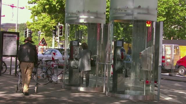 ws woman using public phone, people walking on street / zurich, switzerland  - public phone stock videos & royalty-free footage