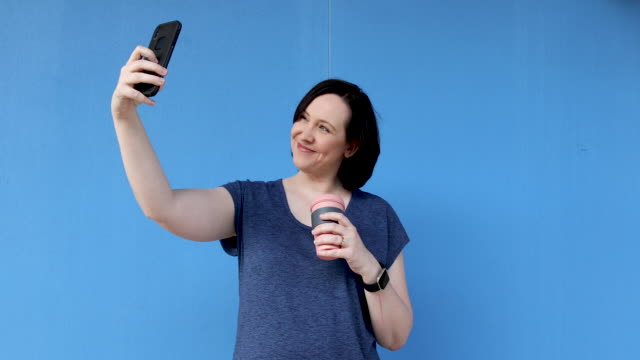 woman using reusable coffee cup and taking selfie - coloured background stock videos & royalty-free footage