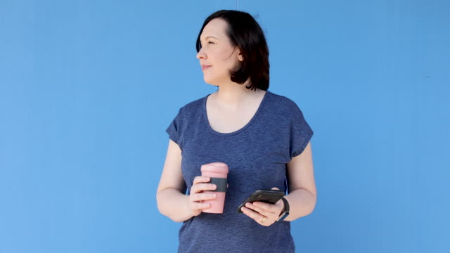 woman using reusable coffee cup - coloured background stock videos & royalty-free footage