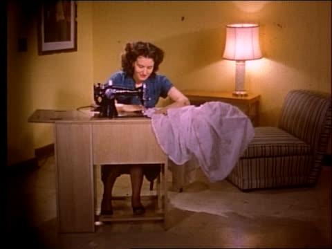 vídeos de stock e filmes b-roll de 1951 woman using sewing machine in house - 1951
