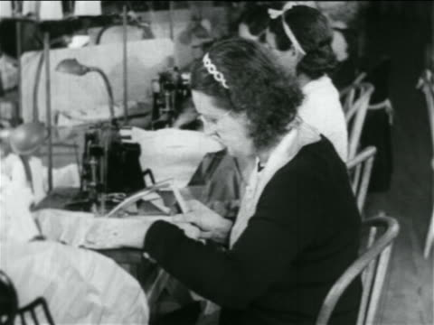 b/w 1934 woman using sewing machine in wpa garment factory / documentary - 雇用促進局点の映像素材/bロール