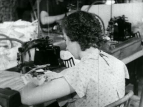 view woman using sewing machine in wpa garment factory / documentary - 雇用促進局点の映像素材/bロール