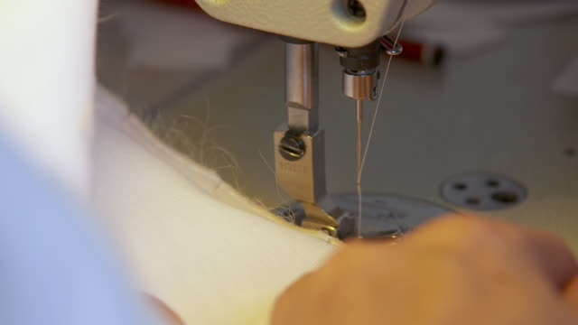 CU Woman using sewing machine on bridal dress / United Kingdom