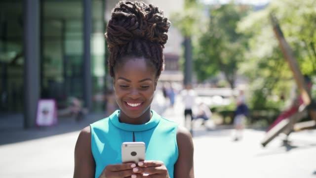 vídeos de stock e filmes b-roll de woman using smart phone and smiling - 30 34 anos