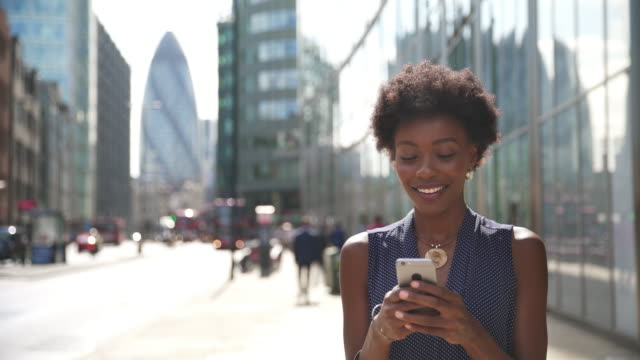 woman using smart phone and smiling - telephone stock videos & royalty-free footage
