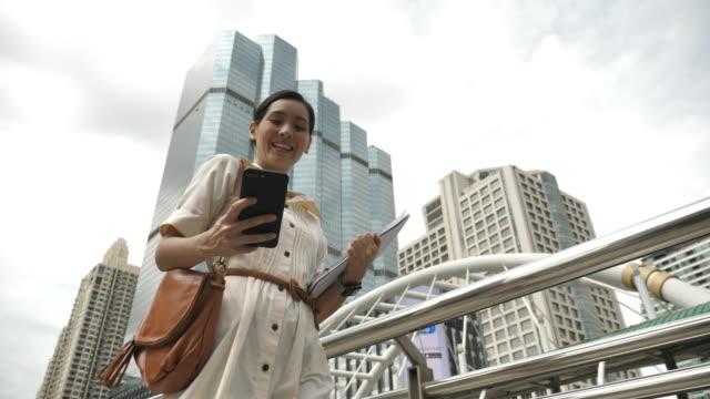 vidéos et rushes de femme utilisant l'application de téléphone intelligent et marchant à l'extérieur près de l'immeuble de bureaux dans la ville - personnes belles