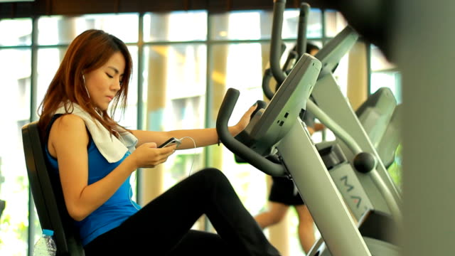 woman using smart phone at gym - in ear headphones stock videos & royalty-free footage