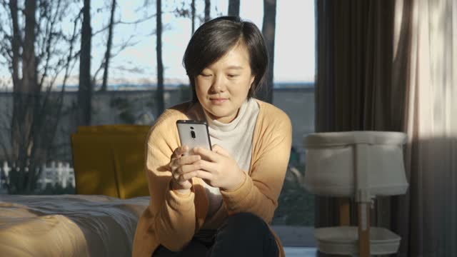 woman using smart phone at home - text messaging stock videos & royalty-free footage