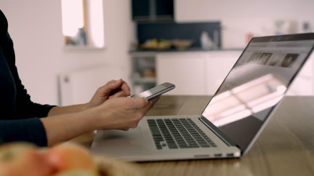 CU Woman using smart phone at laptop