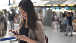 Woman using smart phone at the airport Check in counter