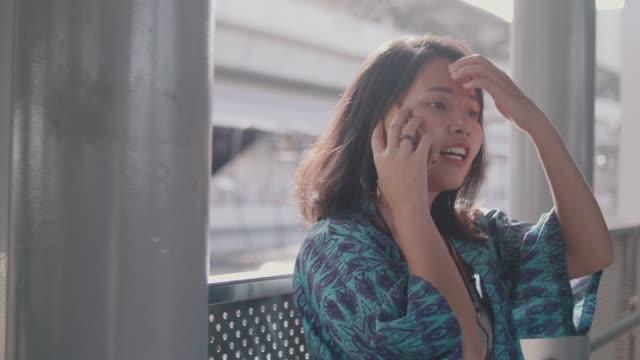 Woman using smart phone at tramway station