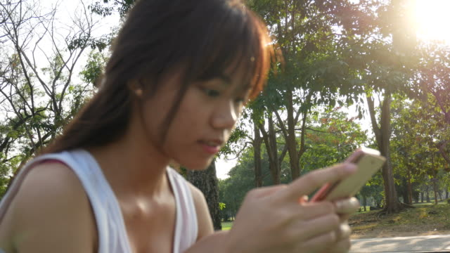 woman using smart phone chat with her friend in garden - motivo floreale video stock e b–roll
