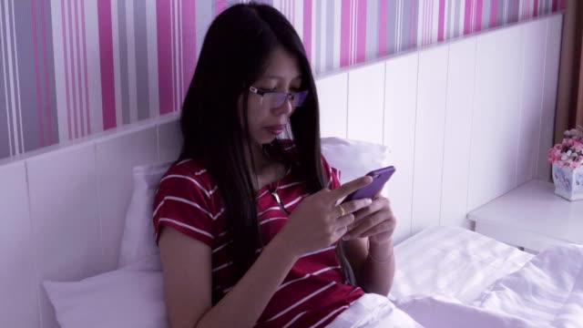 vidéos et rushes de femme à l'aide de téléphone intelligent check-up d'un média social dans son lit le matin - seulement des jeunes femmes