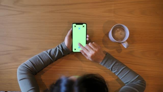 kvinna använda smart telefon visar med grön skärm, chroma nyckel - över axel perspektiv bildbanksvideor och videomaterial från bakom kulisserna