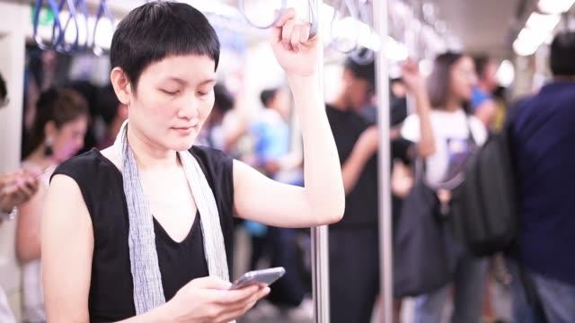 Frau nutzt Smartphone für Online-Kommunikation in U-Bahn-Zug in der Stadt