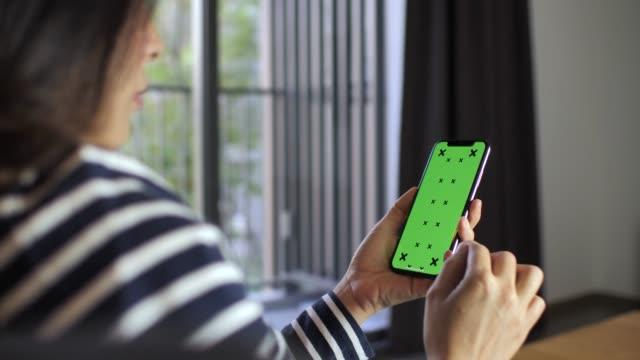 vídeos de stock, filmes e b-roll de mulher inteligente usando telefone verde tela em casa - modelo web