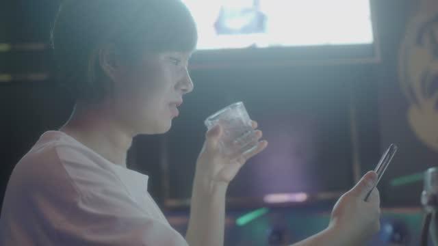 バーでスマートフォンを使用している女性 - ワインバー点の映像素材/bロール