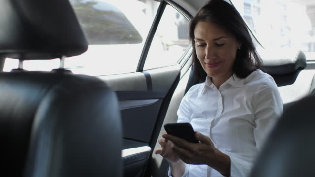 woman using smart phone in car - taxi stock videos & royalty-free footage