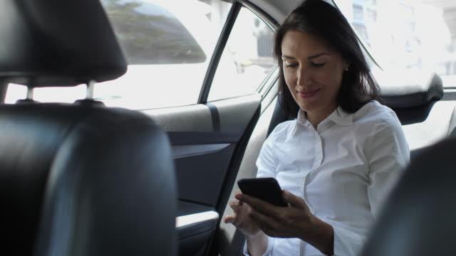 vídeos y material grabado en eventos de stock de mujer usando smart phone en el coche - taxi