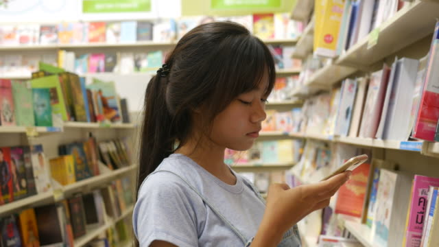 woman using smart phone in librely - book shop stock videos & royalty-free footage