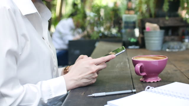 woman using smart phone in outdoor coffee shop - coffee shop background stock videos & royalty-free footage