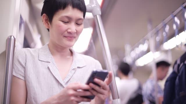 vidéos et rushes de femme utilisant le téléphone intelligent dans le métro ou le train - passager