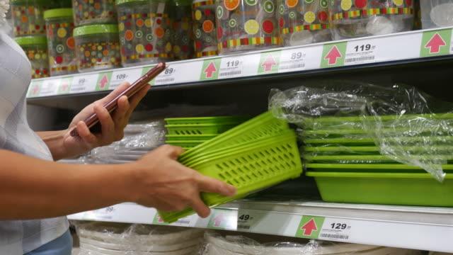 vídeos de stock, filmes e b-roll de mulher usando telefone inteligente no supermercado - artigo de decoração