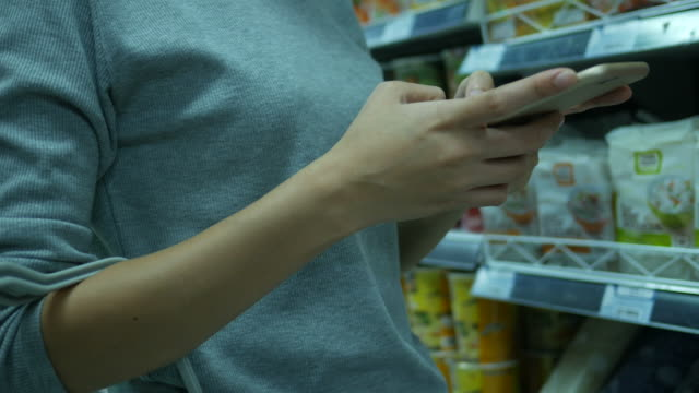 Woman using smart phone in supermarket