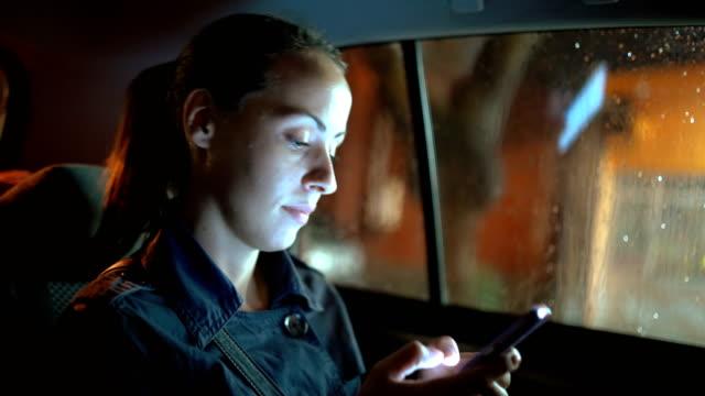 woman using smart phone in the car - passeggero video stock e b–roll