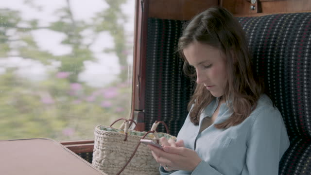 woman using smart phone in train - bag stock videos & royalty-free footage
