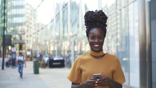 vídeos y material grabado en eventos de stock de woman using smart phone, looks up and smiles at camera. - empleado administrativo