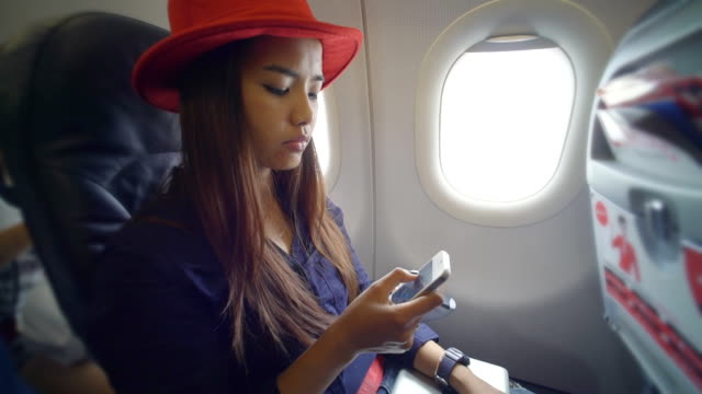 Woman using smart phone on airplane